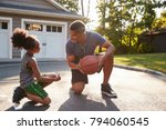 father teaching son how to play ... | Shutterstock . vector #794060545