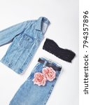 Small photo of Woman's all jean outfit with jean jacket and mom jeans with black belt and crop top or bandeau isolated on white background. Copy space. Flat lay. Top view
