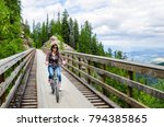 Young Woman Riding a Bicycle across a Wooden Testle Bridge on a Cloudy -Spring Day. Kelowna, BC, Canada.