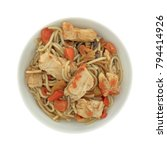 Small photo of Top view of a bowl of sliced chicken breast with angel hair pasta in a tomato sauce isolated on a white background.