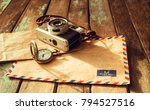 Small photo of Vintage travel background concept, old film camera, antique watches and airmail letter on wood table, instagram effect filter