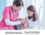 nurse in pink uniform giving an ... | Shutterstock . vector #794729305