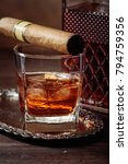 Small photo of Glass of scotch whiskey with natural ice and cigar on old wooden table.