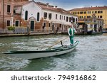 Small photo of Venice, Italy - 9 October 2013: beautiful typical view of the Venice canal with a gondolier sailing on his gondola down the canal on a fine sunny day, charms and splendor of this eternal city