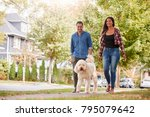 Stock photo couple walking dog along suburban street 795079642