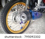 Small photo of BANGKOK, THAILAND - JANUARY 02, 2018: Thoroughly cleaned and detailed light motorcycle drive wheel and exhaust muffler with various aftermarket customization