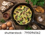 Small photo of omelette with mushrooms on cast iron pan, top view, wooden background