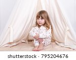 small sad girl sits at a tent... | Shutterstock . vector #795204676