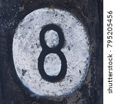 Small photo of The number eight stencil on the surface of a concrete pillar. Close-up black text number eight on background painted white. Inscription number eight on weathered concrete background.