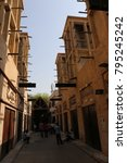 Small photo of View of ancient wind towers in Old Dubai in UAE, al fahidi district. Narrow street with traditional aeration system at the top of the beige houses. Architectural picture taken on 18th July 2015.