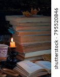 Small photo of stack of old tattered book on a wooden table lighted candle and glasses
