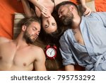 Small photo of Swinger relations, relax, wake up. men and woman with long hair, lover. Family trust, polygamy, betrayal. people lovers sleep at alarm clock, time. Love triangle and romance, perfect morning. friends