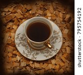 Small photo of cup on saucer with coffee standing on alder chips