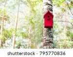 The Red Birdhouse On A Tree In...