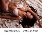 Stock photo sexy model in lingerie lying on satin 795851692