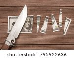 Small photo of A one hundred dollar denomination cut into pieces using a knife against the background of a wooden table. division of finance.