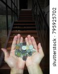Small photo of Man hand holding silver and golden coins with staircase background double exposure style concept for earning, aspiration, starting business