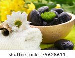 Spa,  flower on the towel, and a bowl with black stones, green tone - stock photo