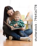 mom reads with child sitting on ... | Shutterstock . vector #796416778