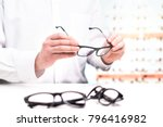 Small photo of Optician in store holding glasses. Eye doctor with lenses. Professional optometrist in white coat with many eyeglasses. Shop interior. Fixing or comparing different options in spectacles.
