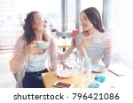 Small photo of Pleasant moment. Happy brunette woman turning her head to her friend and keeping smile on face while joking all the time