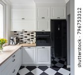 Stock photo small white kitchen with modern chess flooring and black fridge 796753312