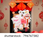 """Small photo of Chinese new year decorating lion dance with """"zhao cai jin bao"""" means """"""""wishing more wealth will coming in"""" greeting card.some """"FU"""" mean""""lucky""""greeting card on the wall"""