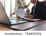 Small photo of Close up of business colleagues reading and comparing documents in office. Businessman sitting at desk holding contract papers with female colleague pointing.