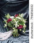 Small photo of Close-up of bouquet of marsala and white flowers with greenery decorated by ribbons, standing on gray velour cloth