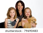 a pretty Mother and her two daughters with a Golden Retriever Puppy. - stock photo