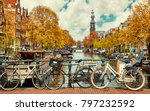 Bike over canal Amsterdam city. Picturesque town landscape in Netherlands with view on river Amstel.