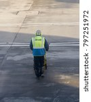 Small photo of Heathrow Airport, London, England - January 2018: Airline operative wearing a high visibility jacket