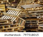 Small photo of A big pile of used/grunge wood pallets placed randomly and dumped in an outdoor area. Old scrapped wooden shipping pallets in a jumbled pile.