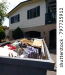 Small photo of Garbage skip in a front yards of a family suburban home full of waste