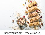 Small photo of Granola bar. Healthy sweet dessert snack. Cereal granola bar with nuts, fruit and berries on a white stone table. Top view copy space.