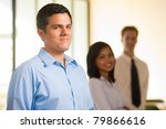 Singled out foreground profile of handsome Hispanic male team leader standing, looking at camera, heads a line of cheerful colleagues behind in background. Horizontal - stock photo