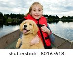 young girl with a cute golden retriever puppy on a boat at a lake. - stock photo