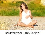 Happy pregnant woman on the beach - stock photo