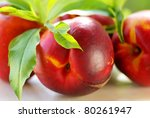 fresh peach fruits with green leaves on green background - stock photo