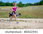 Stock photo woman runner running with a dog on country road 80322541