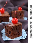 brownie chocolate cakes with cherries on a brown background - stock photo