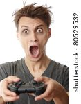 Crazy man in trouble playing video game using joystick - stock photo