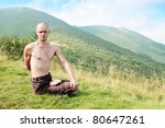 Young man is occupied yogi in the foot of the mountains - stock photo