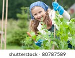 Gardening - little girl  working in vegetable garden - stock photo