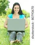 Beautiful happy student using laptop outdoors. - stock photo