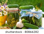 jars of homemade preserves with pickled cucumbers on the table in the garden - stock photo