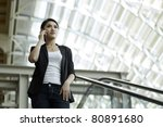 Asian Business woman using a Cell Phone - stock photo