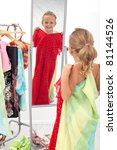 Trying on dresses is fun - little girl in front of the mirror - stock photo