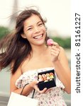 Paris woman eating macarons in Paris happy and smiling. Eiffel tower in the background. Cute beautiful mixed race Asian Caucasian female model playful in dress summer dress holding small shopping bag. - stock photo