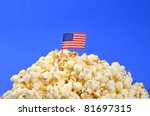 American Flag and popcorn/ American Snack/American flag on a pile of poppcorn - stock photo